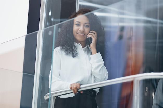 Lächelnde junge frau, die auf ihrem smartphone chattet, während sie im aufzug nach oben fährt