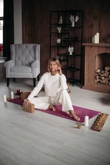 Lächelnde junge frau, die auf sportmatte sitzt, bevor sie zu hause mit yoga beginnt. gesundes und lifestyle-konzept