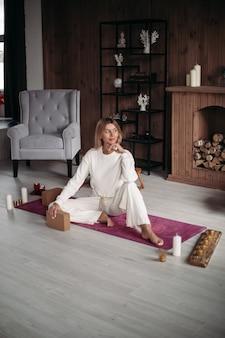 Lächelnde junge frau, die auf sportmatte sitzt, bevor yoga zu hause anfängt. gesundes und lifestyle-konzept