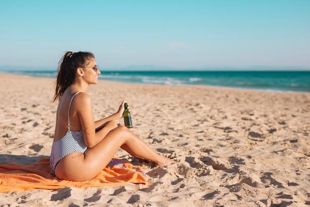 Lächelnde junge frau, die auf strand mit bier sich entspannt