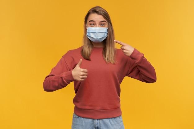Lächelnde junge frau, die auf virusschutzmaske im gesicht gegen coronavirus zeigt und daumen oben über gelber wand zeigt