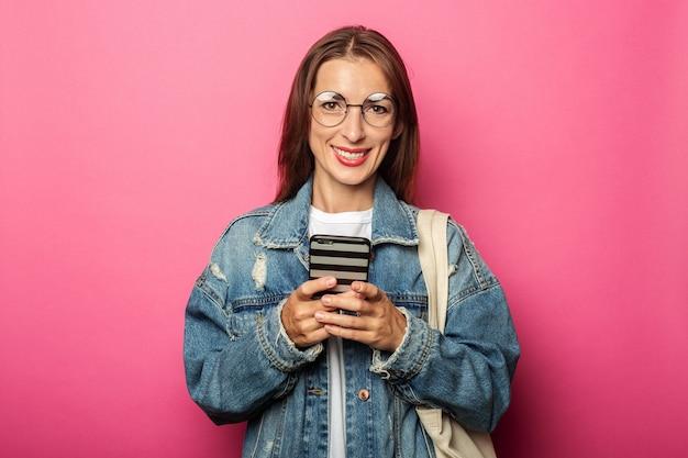 Lächelnde junge frau, die brille und jeansjacke mit telefon trägt