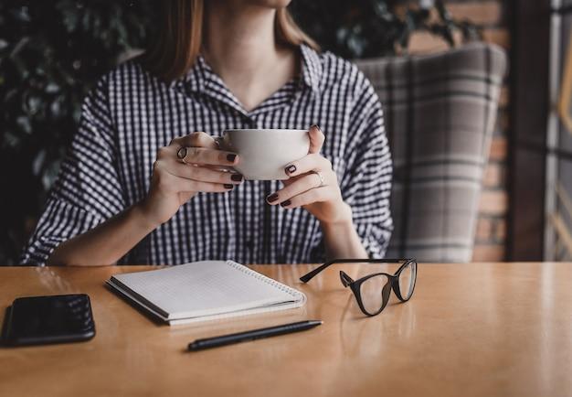 Lächelnde junge frau, die brillen beim mit kaffeetasse im café bei tisch sitzen hält