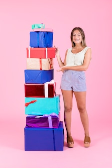 Lächelnde junge frau, die bunten stapel geschenkboxen auf rosa hintergrund darstellt