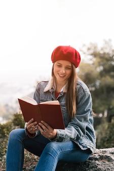 Lächelnde junge frau, die das buch an draußen liest