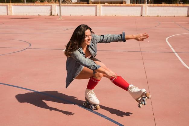 Lächelnde junge frau, die das weibliche schlittschuhläuferbalancieren trägt
