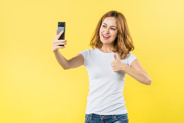 Lächelnde junge frau, die daumen herauf das zeichen nimmt selfie am intelligenten telefon gegen gelben hintergrund zeigt