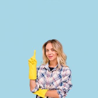 Lächelnde junge frau, die den gelben handschuh zeigt aufwärts steht gegen blaue wand trägt