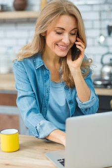 Lächelnde junge frau, die den laptop spricht am intelligenten telefon verwendet