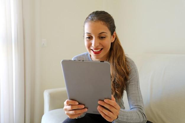 Lächelnde junge frau, die den tablet-pc-computer betrachtet, der zu hause sitzt