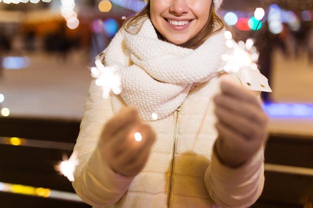 Lächelnde junge frau, die den winter trägt, strickte kleidung, die draußen wunderkerze über schneehintergrund hält. weihnachtsferien.