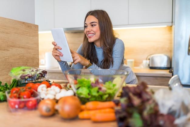 Lächelnde junge frau, die digital-tablet mit gemüse auf countertop in der küche verwendet