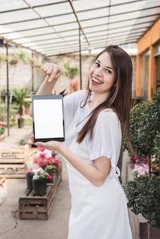 Lächelnde junge frau, die digitale tablette mit leerem weißem schirm im gewächshaus zeigt