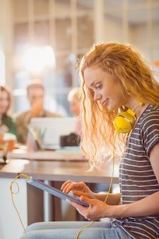 Lächelnde junge frau, die digitale tablette verwendet