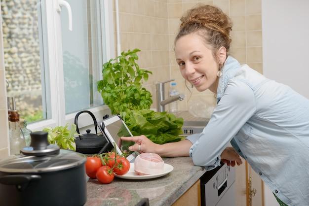 Lächelnde junge frau, die eine tablette für das kochen verwendet
