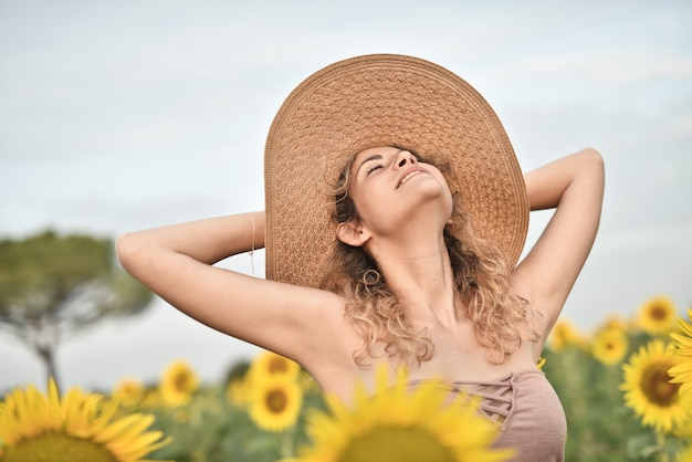 Lächelnde junge frau, die einen hut im sonnenblumenfeld trägt - das konzept des glücks