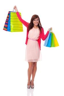 Lächelnde junge frau, die einkaufstaschen hochhält