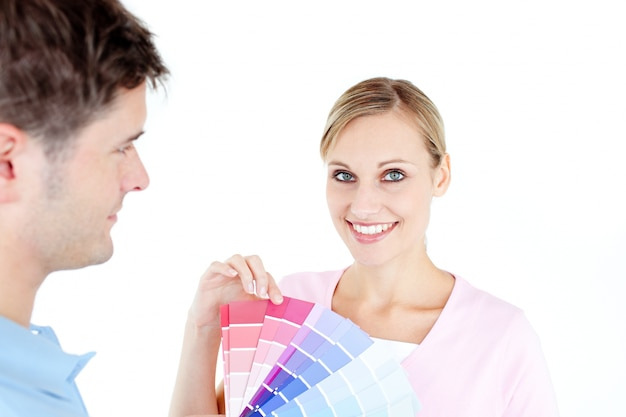 Lächelnde junge frau, die farben für das malen eines raumes wählt