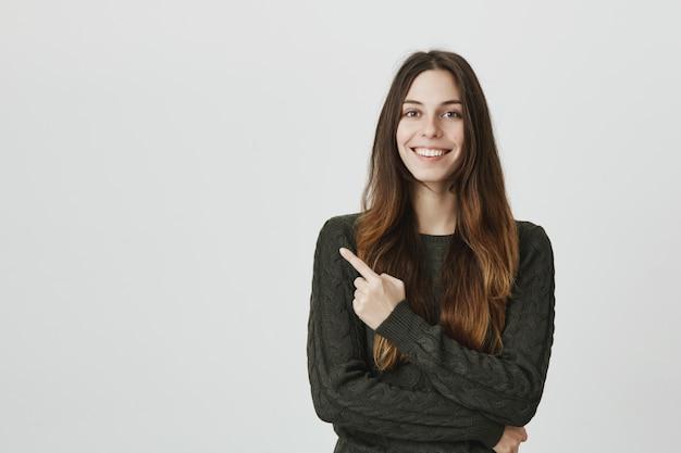 Lächelnde junge frau, die finger oben links zeigt und werbung zeigt