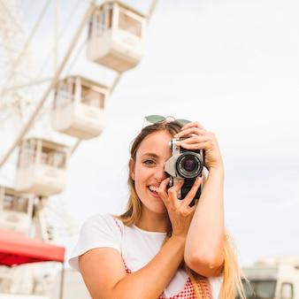 Lächelnde junge frau, die fotos mit kamera am vergnügungspark macht