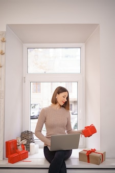 Lächelnde junge frau, die freunde mit weihnachten im video-chat auf laptop mit geschenkboxen begrüßt