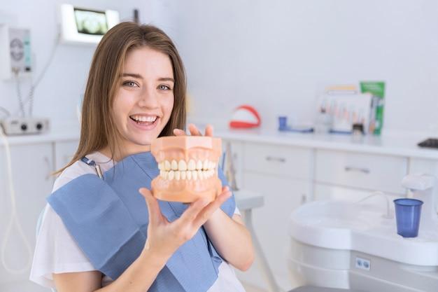 Lächelnde junge frau, die gebiss in ihren händen an der zahnmedizinischen klinik hält