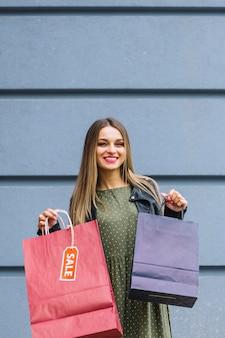 Lächelnde junge frau, die gegen die wand hält purpurrote und rote einkaufstaschen steht