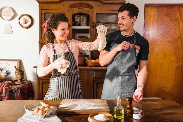 Lächelnde junge frau, die gekneteten teig zu ihrem ehemann zeigt