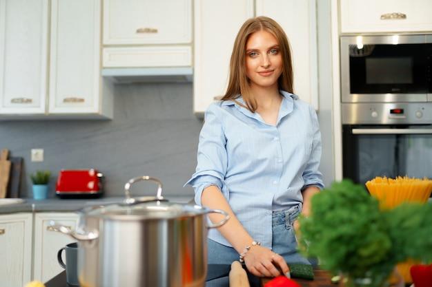 Lächelnde junge frau, die gemüse für salat in der küche schneidet