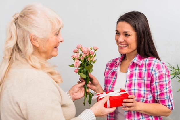 Lächelnde junge frau, die geschenk und rosafarbenen blumenstrauß von ihrer älteren frau nimmt