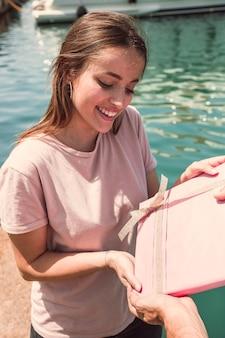 Lächelnde junge frau, die geschenk von ihrem freund am hafen empfängt