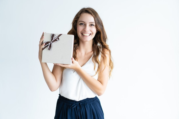 Lächelnde junge frau, die geschenkbox mit band hält