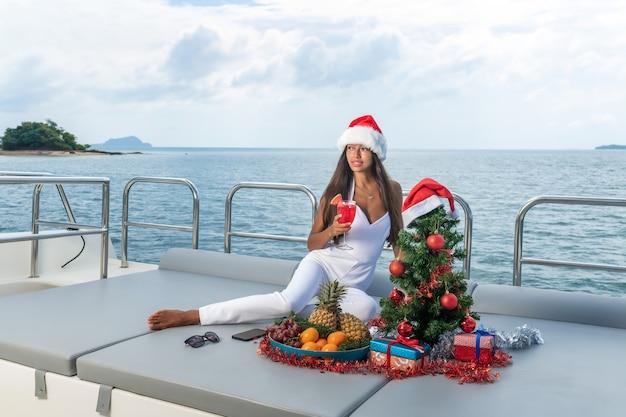 Lächelnde junge frau, die getränke trinkt und tropische früchte für weihnachten während auf einer yachtkreuzfahrt isst.