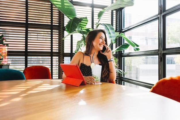 Lächelnde junge frau, die glas cocktail spricht am intelligenten telefon im restaurant hält