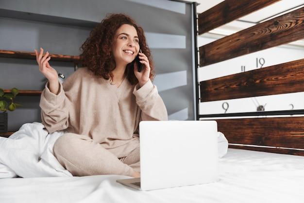 Lächelnde junge frau, die hauskleidung mit laptop und handy trägt, während sie zu hause auf weißer bettwäsche im bett sitzt