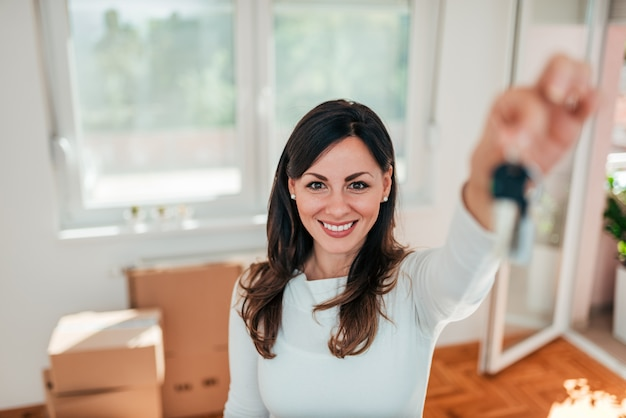Lächelnde junge frau, die hausschlüssel ihres neuen hauses hält. immobilien- und umzugskonzept.