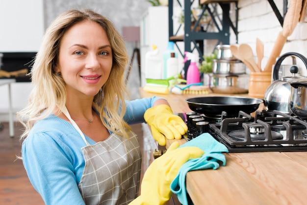 Lächelnde junge frau, die hölzerne küchenarbeitsplatte abwischt