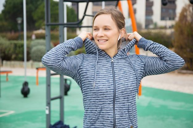 Lächelnde junge frau, die hoodiehaube auf sportplatz setzt