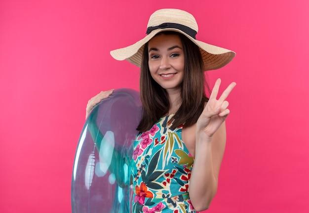 Lächelnde junge frau, die hut hält, der schwimmring hält und friedenszeichen auf isolierter rosa wand zeigt