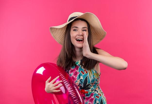 Lächelnde junge frau, die hut hält, der schwimmring hält und hand nahe mund auf lokalisierter rosa wand hält