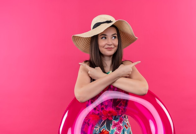 Lächelnde junge frau, die hut hält, der schwimmring hält und mit den fingern an den seiten auf isolierter rosa wand zeigt