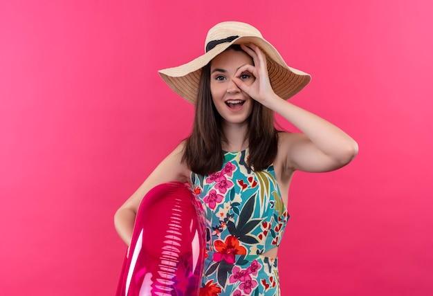 Lächelnde junge frau, die hut hält, der schwimmring hält und ok zeichen auf isolierter rosa wand tut