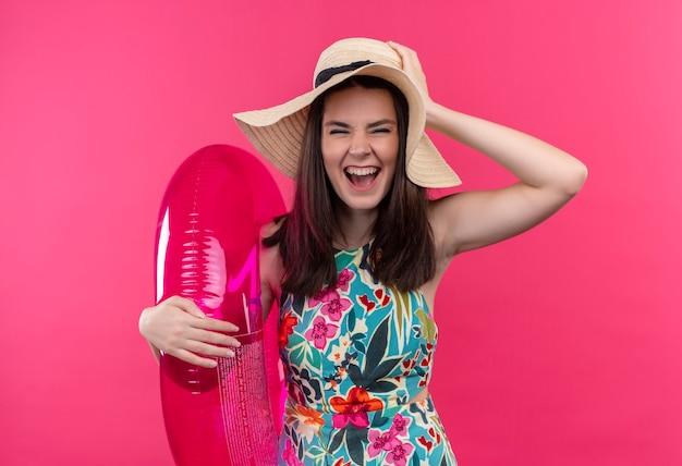 Lächelnde junge frau, die hut hält, der schwimmring hält und rockzeichen auf isolierter rosa wand zeigt