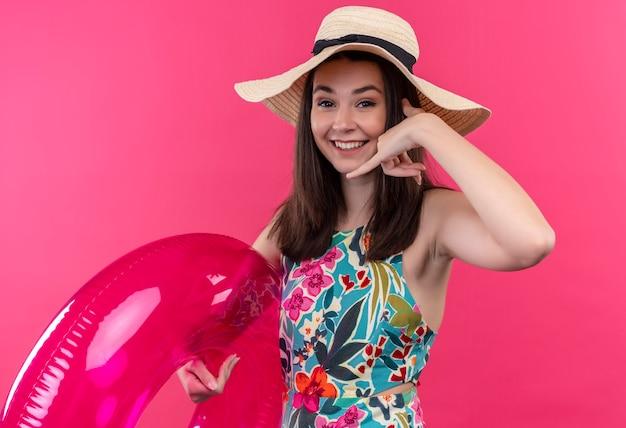 Lächelnde junge frau, die hut hält, der schwimmring hält und telefonzeichen auf isolierter rosa wand tut