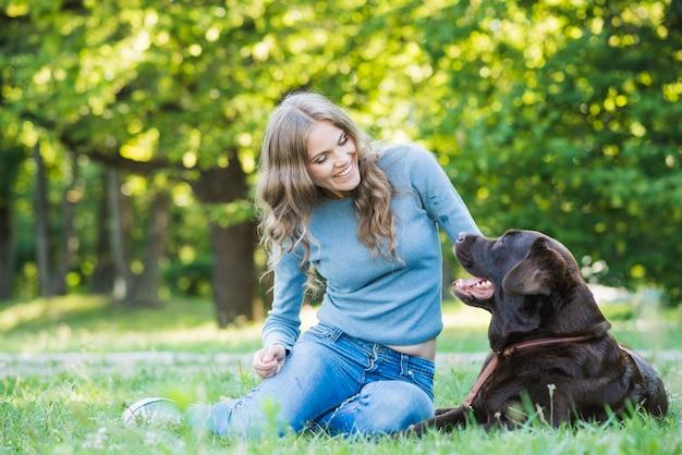 Lächelnde junge frau, die ihren hund im park betrachtet