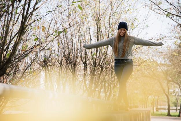 Lächelnde junge frau, die im park balanciert
