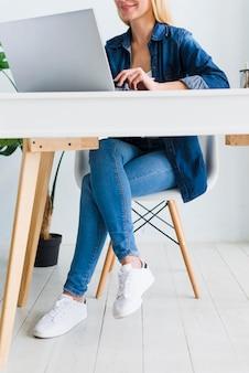 Lächelnde junge frau, die im stuhl nahe laptop sitzt