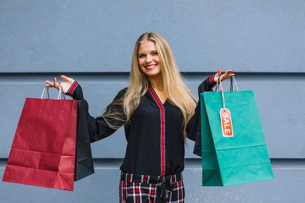 Lächelnde junge frau, die in der hand bunte einkaufstaschen anbietet