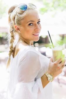 Lächelnde junge frau, die in der hand latte macchiato glas hält