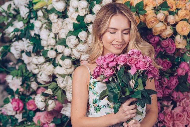 Lächelnde junge frau, die in der hand schöne rosa rosen hält